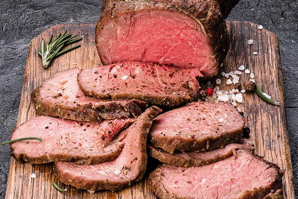 bison roast with garlic on a cutting board